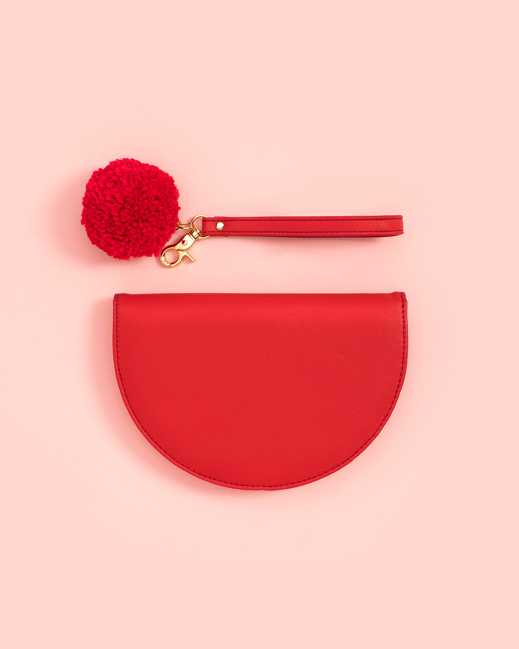 Removable wristlet keychain with synthetic wool pom pom attaches to metallic gold zipper pull.