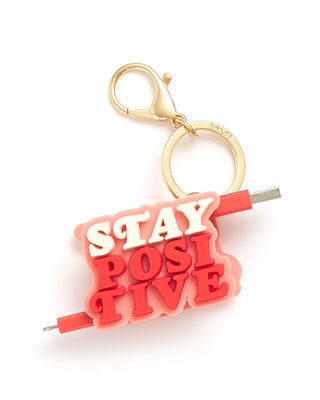 This Retractable Charging Cord features a red and white body that spells 'Stay Positive'.