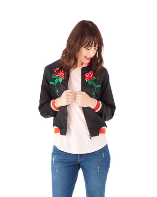 woman in jeans wearing a black bomber jacket with embroidered roses