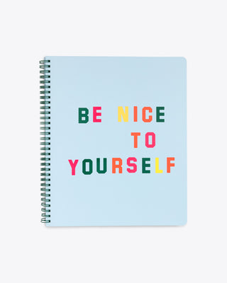 large notebook featuring a light blue cover with the words be nice to yourself, in various colors