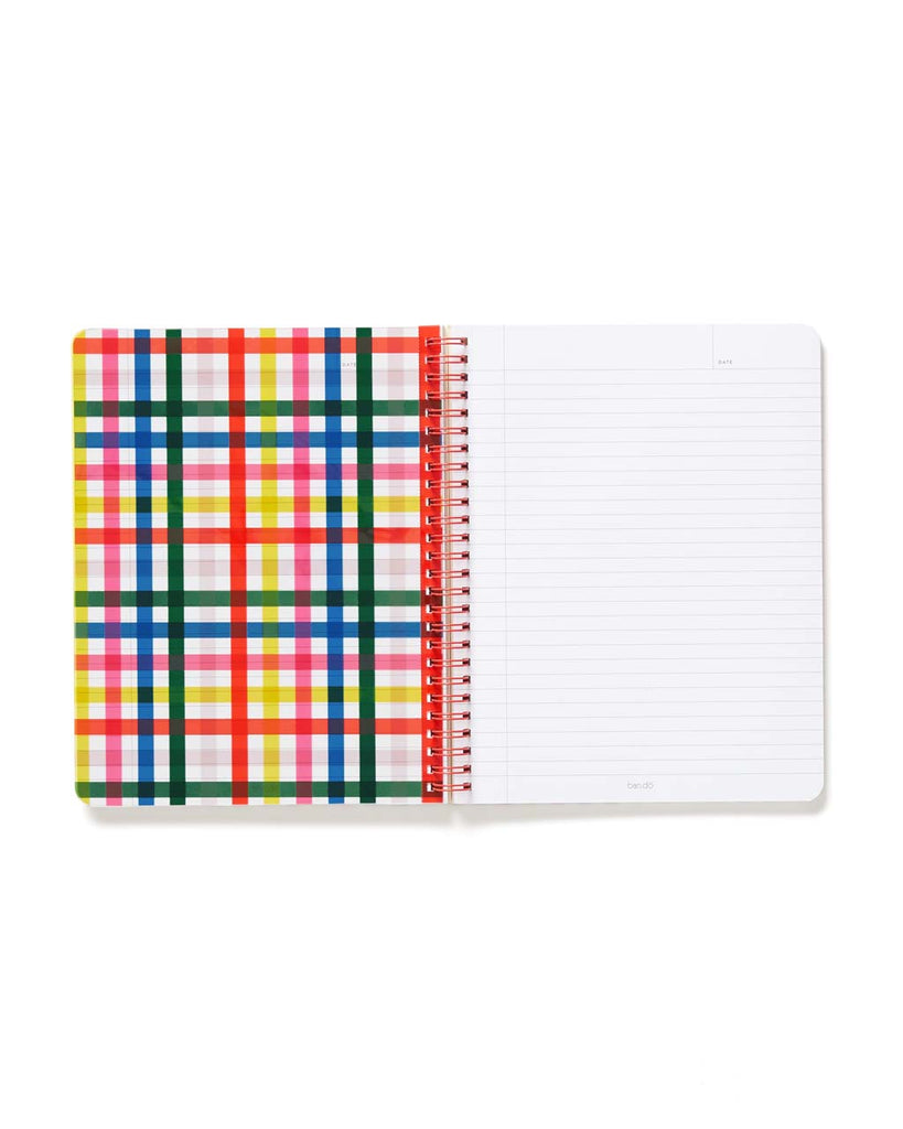 Interior cover of notebook with red, blue, green, yellow and pink plaid to the left, and the first ruled page to the right