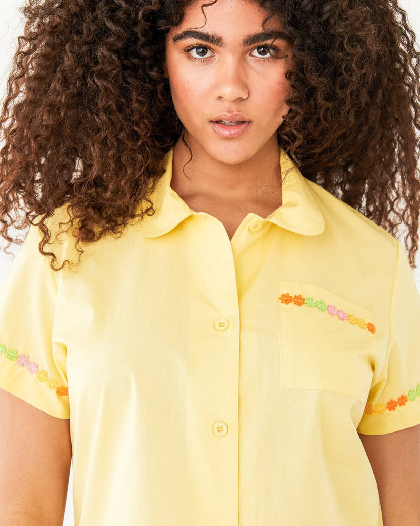 close up of model wearing yellow short sleeve leisure shirt with a daisy applique on the trim of sleeves and patch pocket