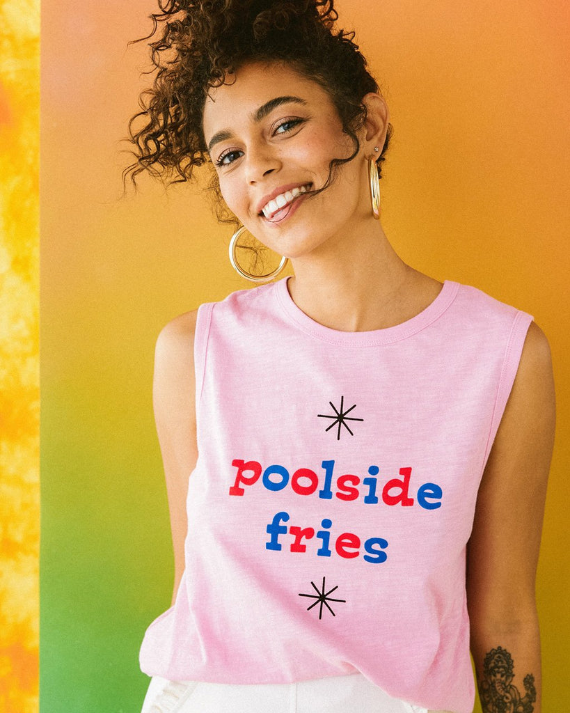 model wearing pink muscle tank with the words poolside fries in red and blue lettering paired with white bottoms