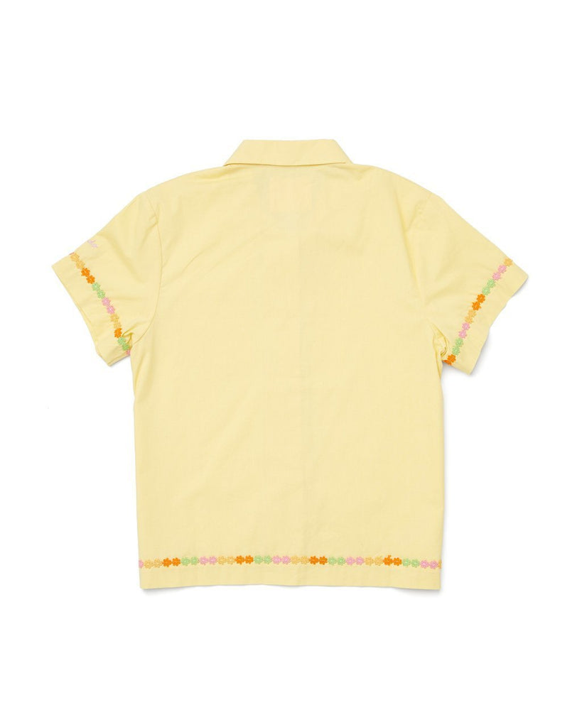 back view of yellow short sleeve leisure shirt with a daisy applique on the trim of sleeves, patch pocket, and bottom