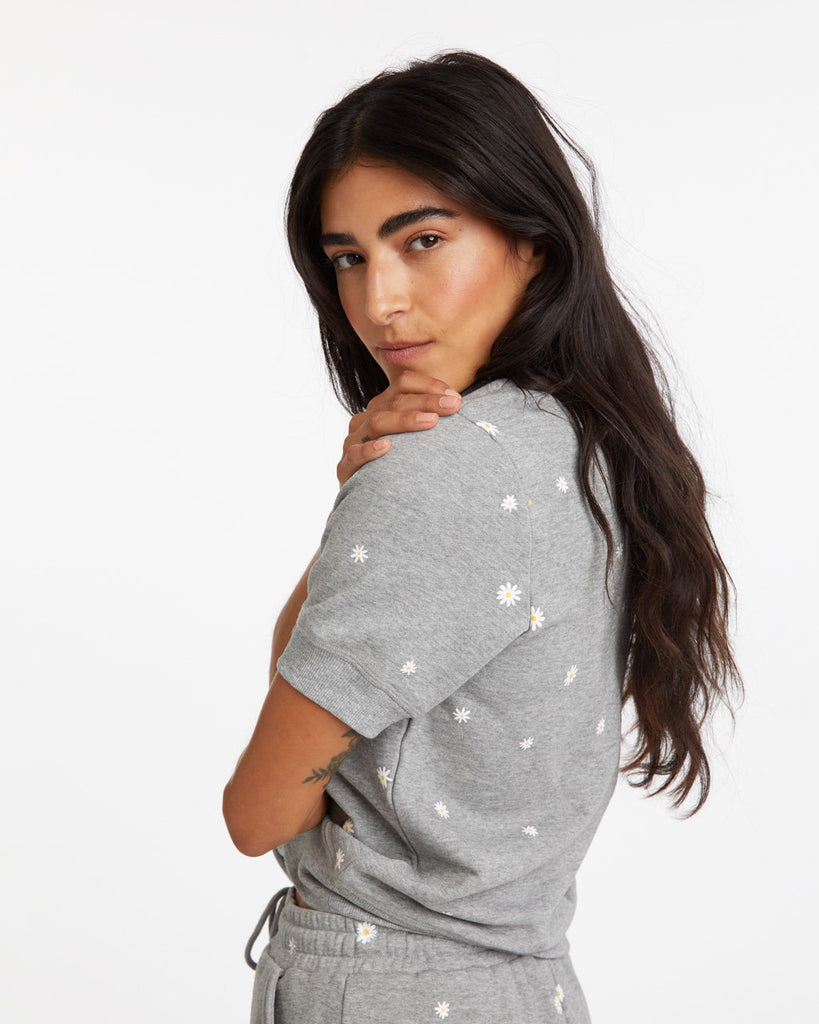 Side view of grey short sleeve sweatshirt with daisy pattern all over