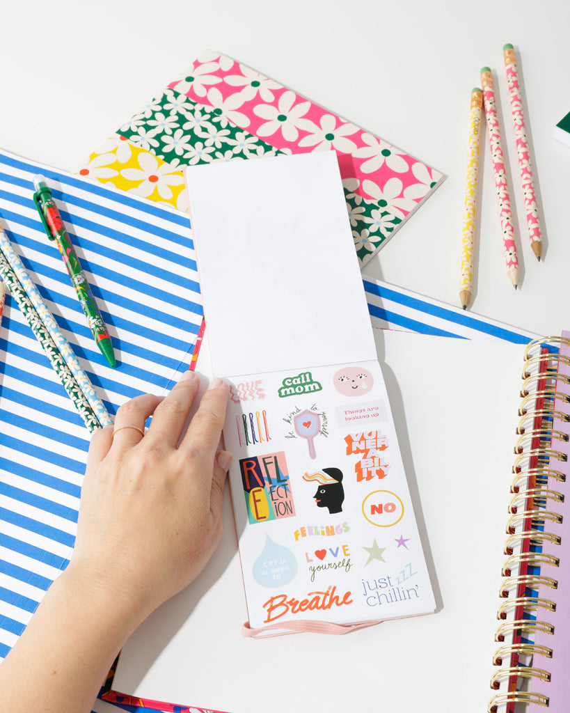 lifestyle image of sticker book shown with a bando planner and other bando products