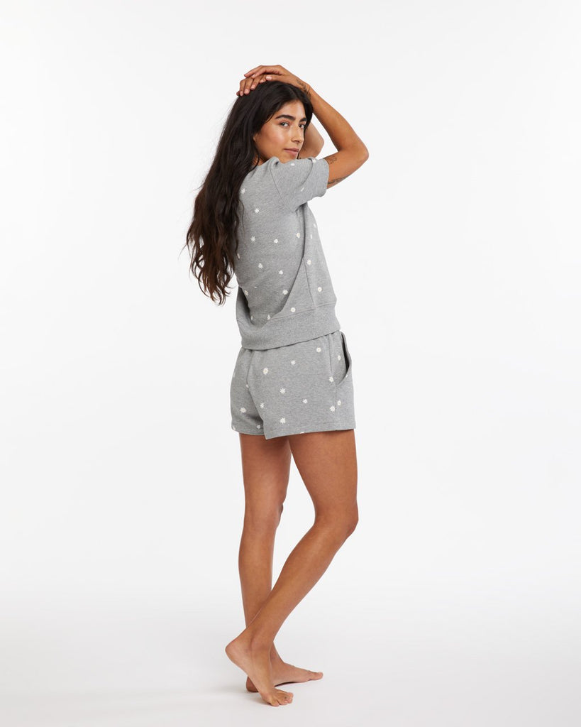 Grey cotton shorts with a daisy pattern all over shown on model with a relaxed fit
