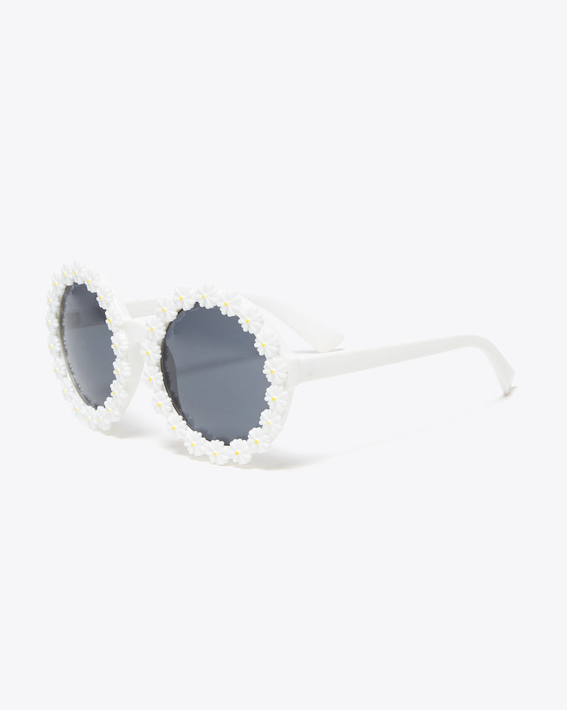 side view of white round sunglasses with a 3D daisy pattern on rim of lenses