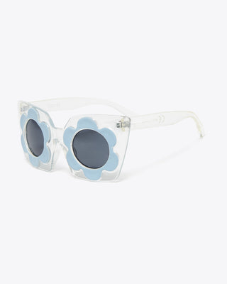 side view of clear cat eye sunglasses with a light blue daisy design on rim of lenses