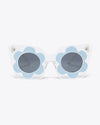 front view of clear cat eye sunglasses with a light blue daisy design on rim of lenses
