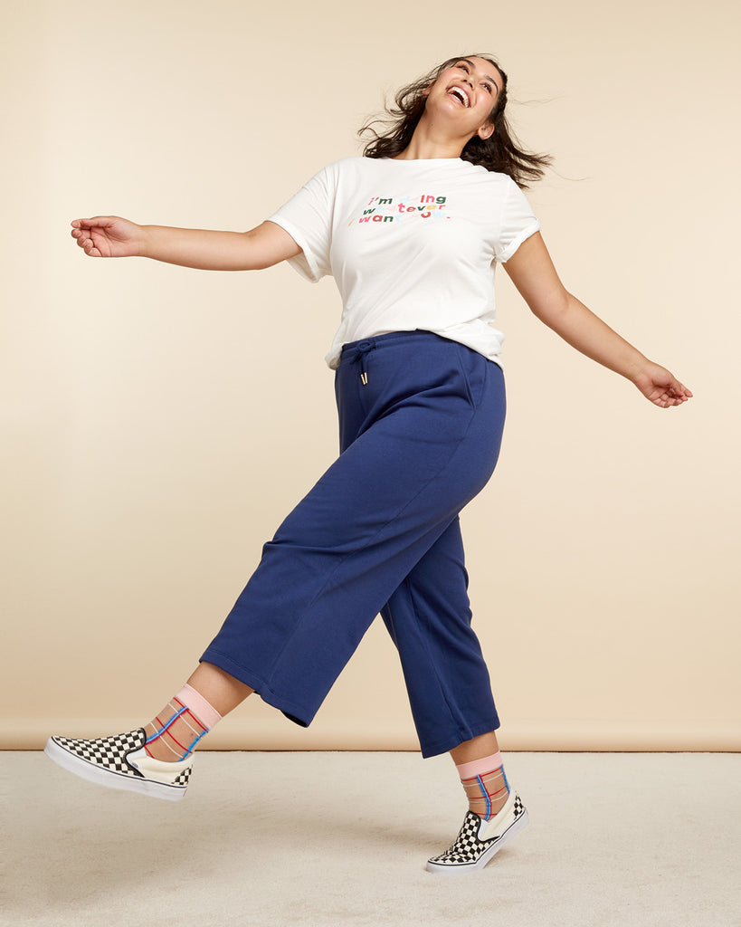 model wearing navy wide leg sweatpants, in motion dancing and smiling