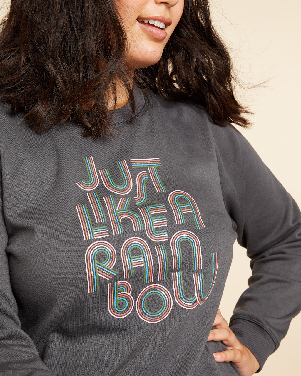 close up image of brunette model shown wearing grey sweatshirt with the words just like a rainbow