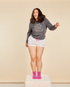 brunette model shown wearing grey sweatshirt with the words just like a rainbow and paired with party dot shorts and hot pink socks