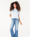 blue slub tee with a patch pocket and the words take really good care of yourself show on model paired with jeans