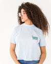 blue slub tee with a patch pocket and the words take really good care of yourself show on model