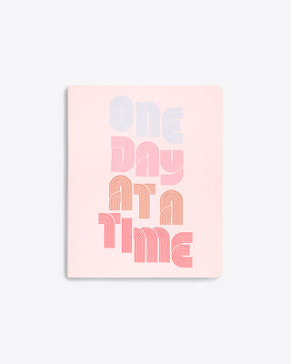 "daily planner cover in blush pink with ""ONE DAY AT A TIME"" text graphic"