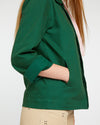side view of model with her hand in the pocket of the dark green work jacket