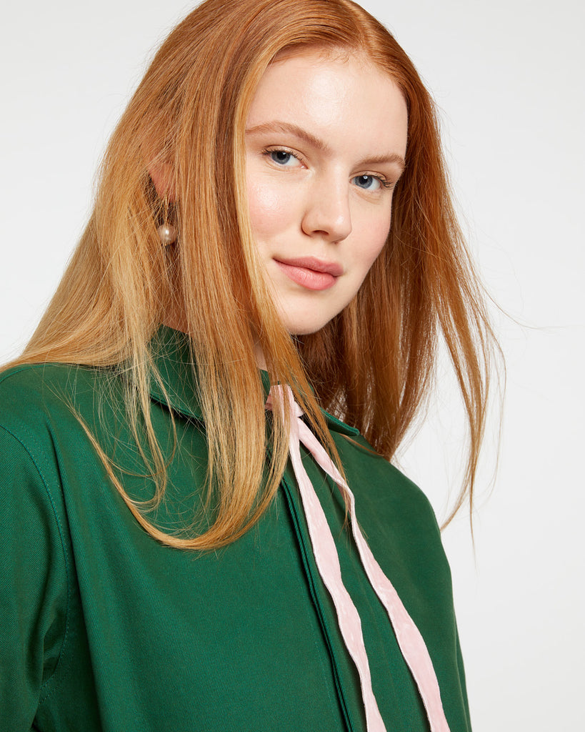 woman with red hair wearing a dark green jacket with a pink tie