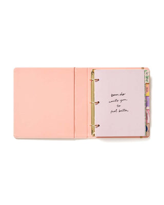 "Pink planner with ""Take Care"" printed on the font cover in gold with a gold elastic closure"