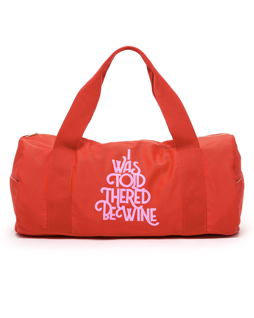 "Red duffle bag with ""I was told there'd be wine"" printed on the front in pink."