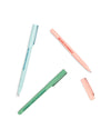 Set of three pens scattered on surface: One blue, one pink, one green