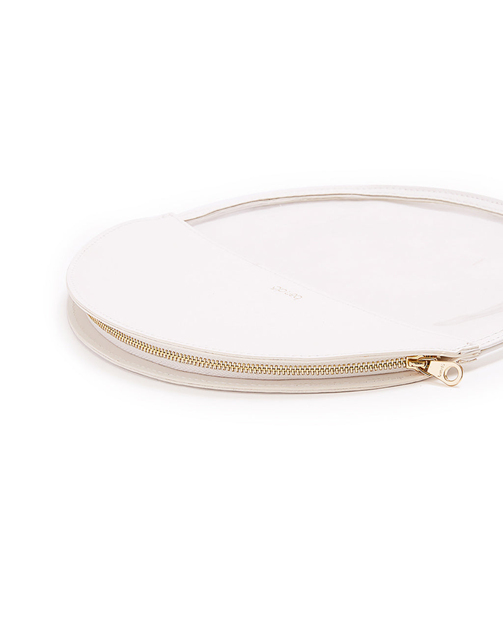 close up of brass zipper on white circle clutch