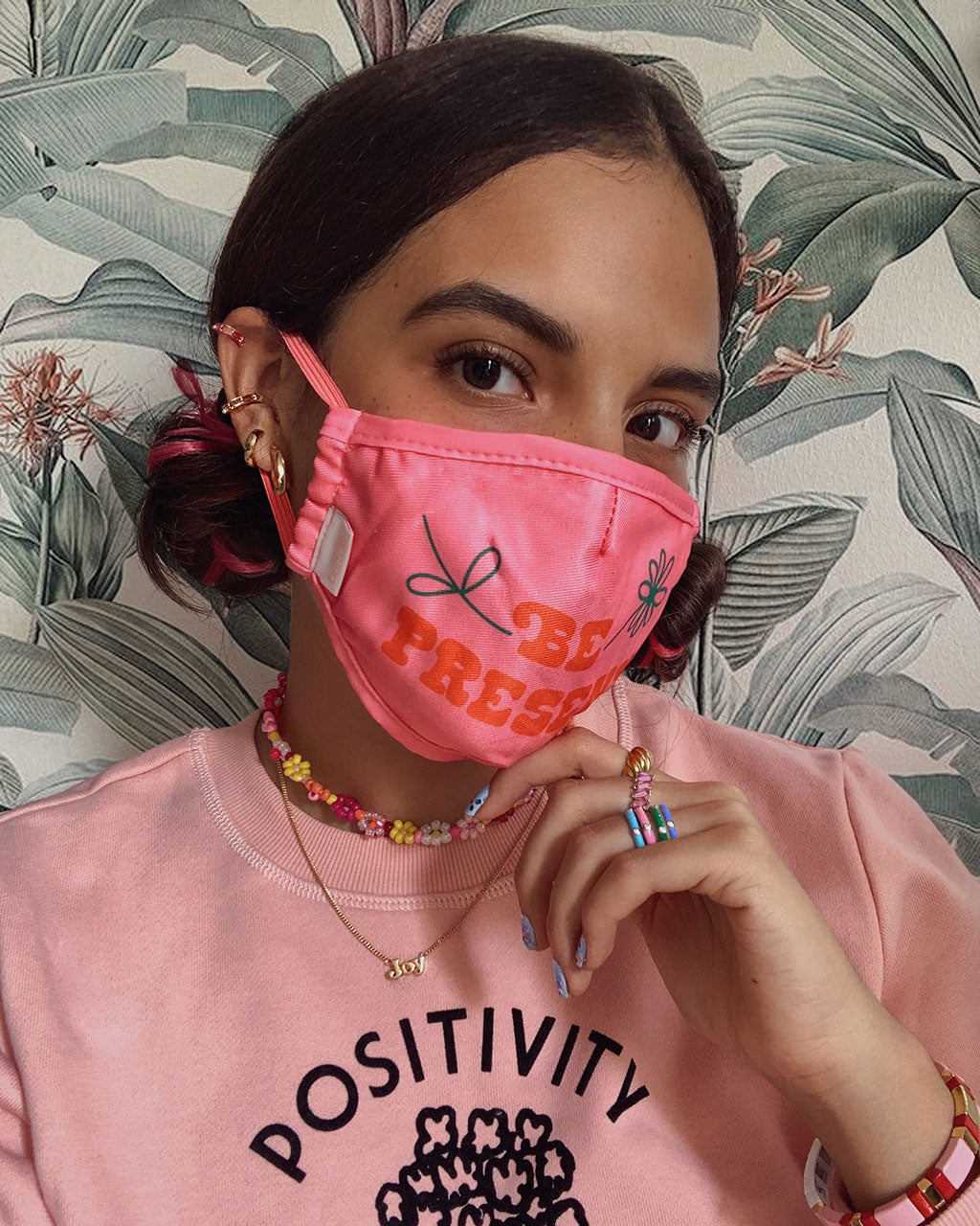 brunette model shown wearing pink face mask with the words be present