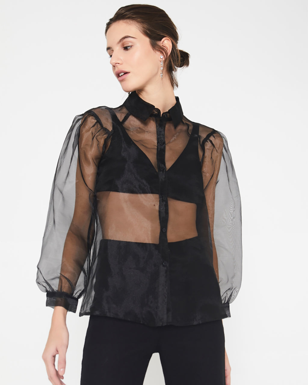 model wearing transparent black blouse with black bra underneath