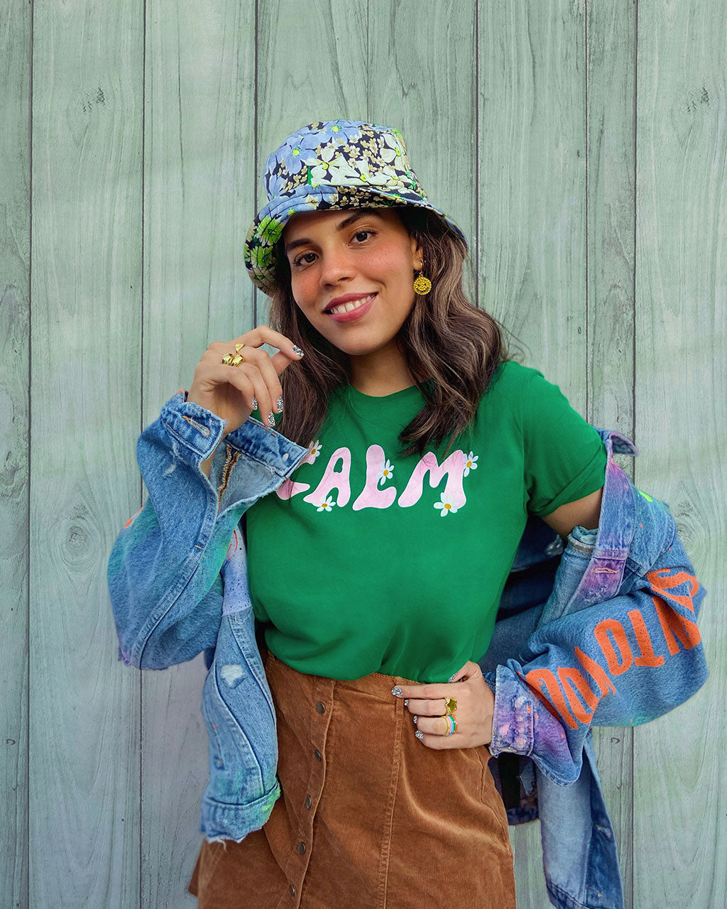 brunette model shown wearing green calm tee paired with jean jacket and brown button up skirt