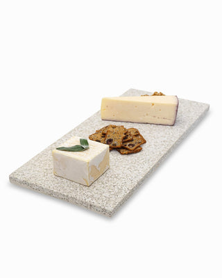 white sand cheese board shown with food