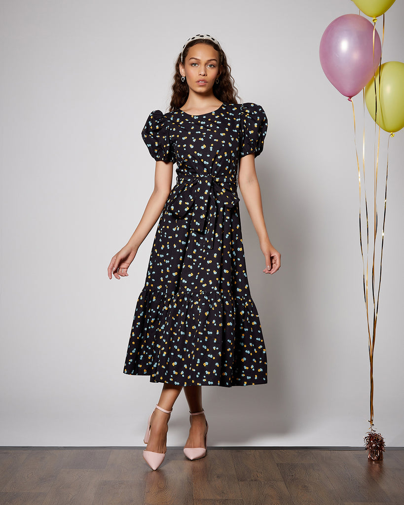 model shown wearing black midi dress with a blue and yellow confetti design