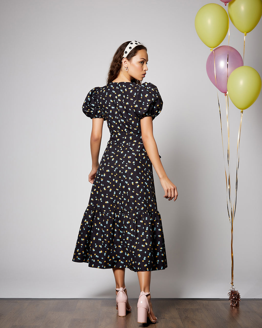 back view of model wearing black midi dress with confetti design