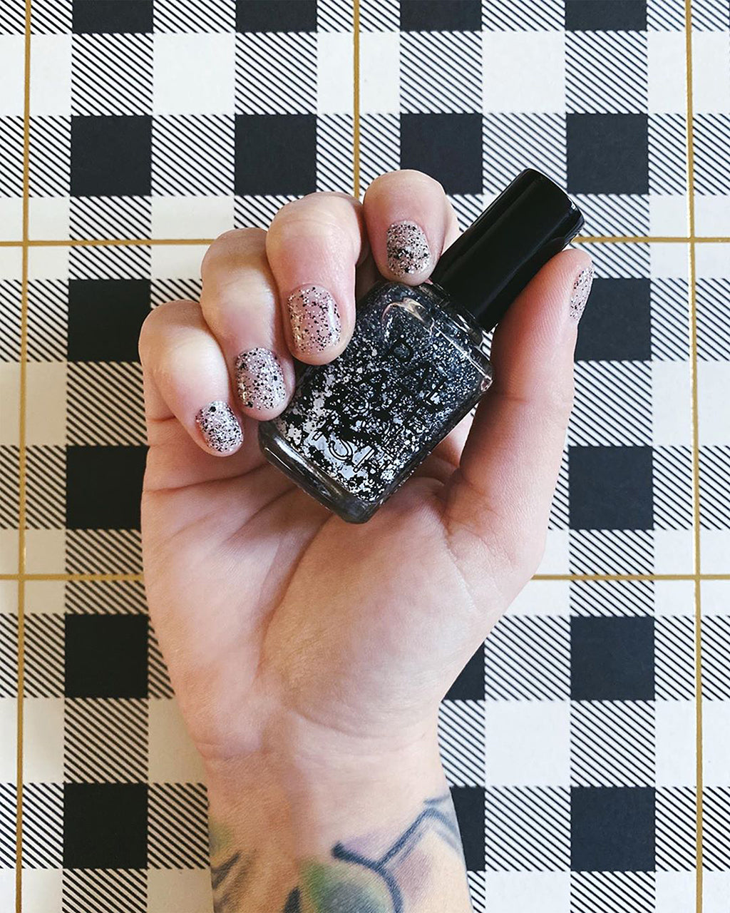 model hands shown holding cookies and cream nail polish bottle and nails painted with polish