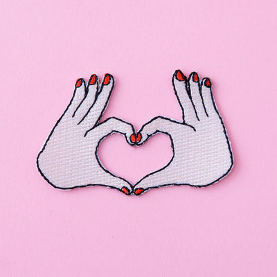 two hands with red nail polish heart love patch