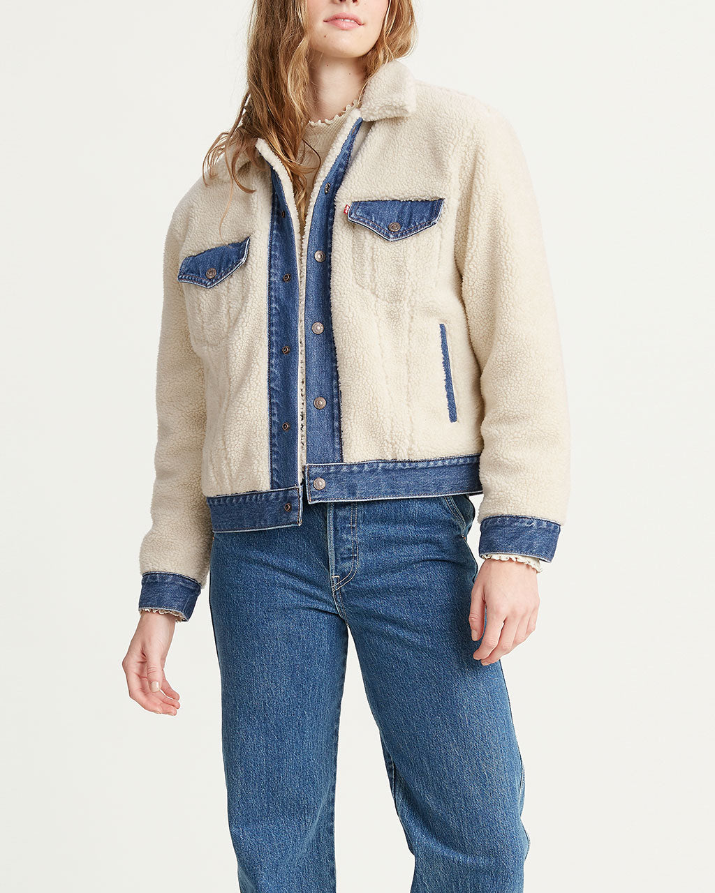 model shown wearing a white sherpa jacket with denim trim