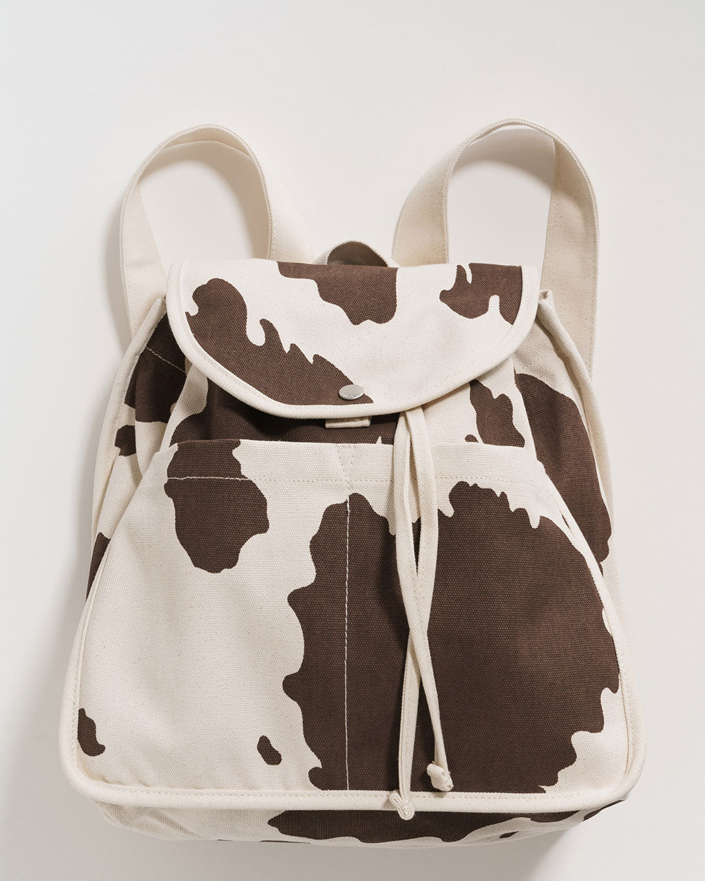 cream canvas backpack with brown cow print