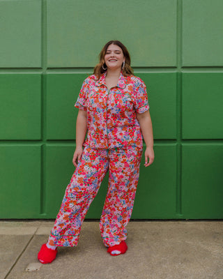woman wearing bright floral pajama set with red fuzzy slippers