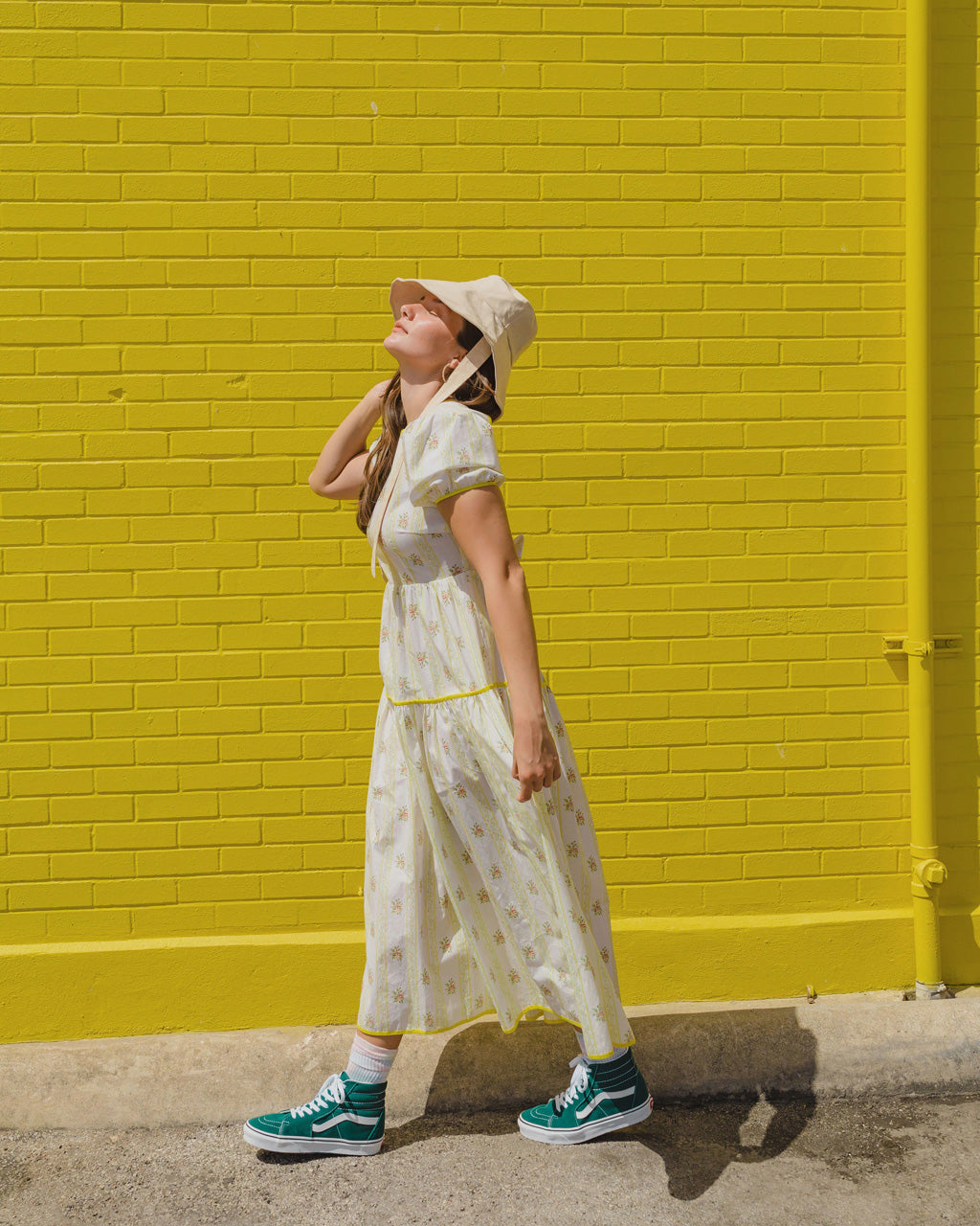 model wearing yellow floral prairie midi dress with green vans sneakers and bucket hat