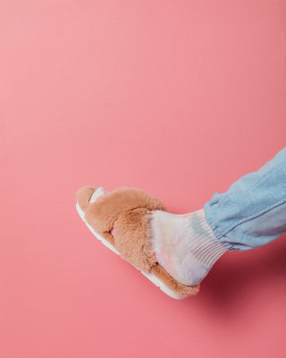 nude fuzzy slipper shown on model's foot with tie dye sock and blue pants