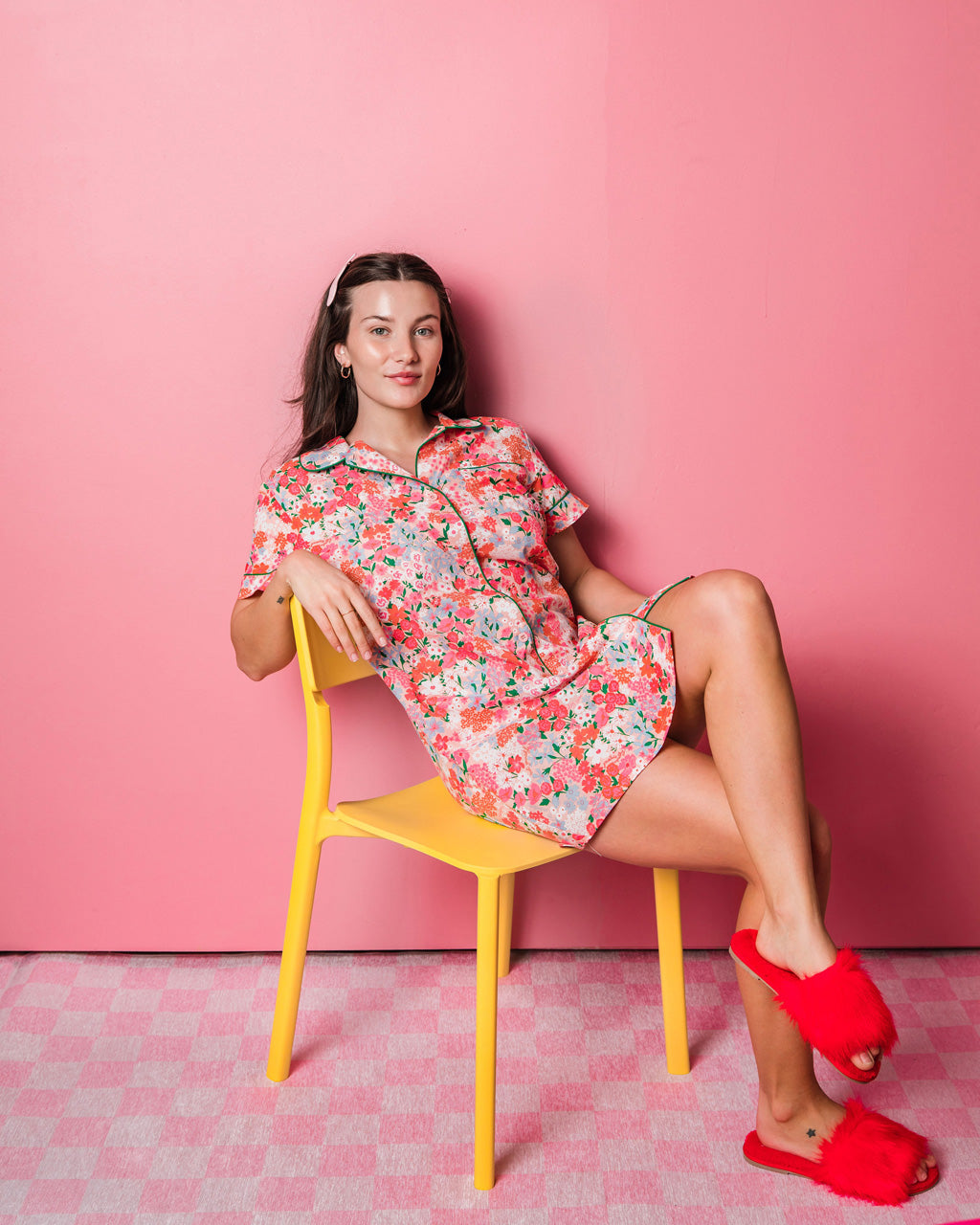 woman wearing bright floral pajama dress with red fuzzy slippers sitting on a yellow chair