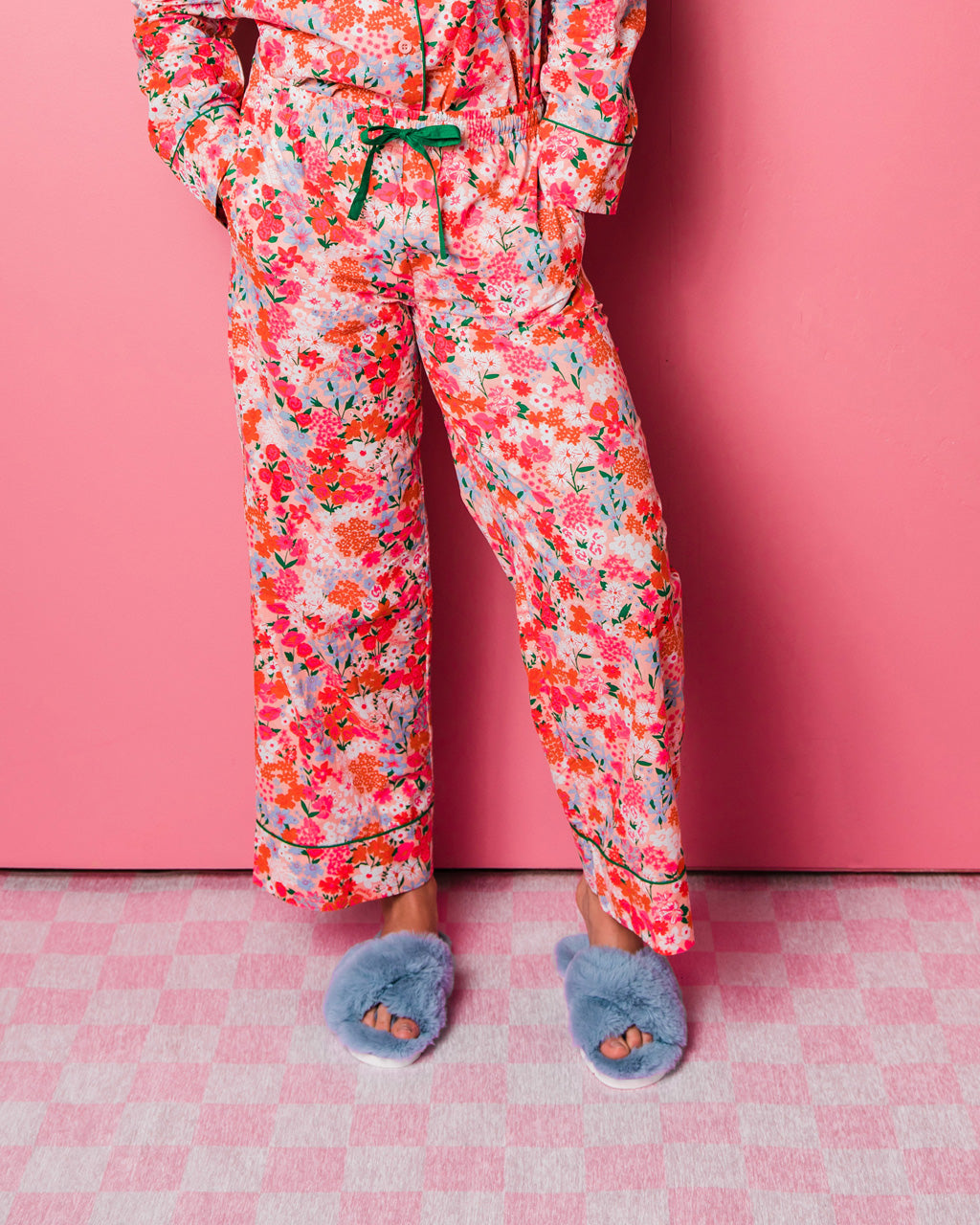woman wearing bright multi color floral leisure pants with blue fuzzy slippers