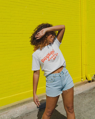 woman wearing white graphic tee with lightwashed denim cutoff shorts