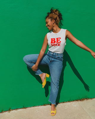 "woman wearing white muscle tank top with ""Be Nice"" graphic in red with blue jeans and yellow slide heels"