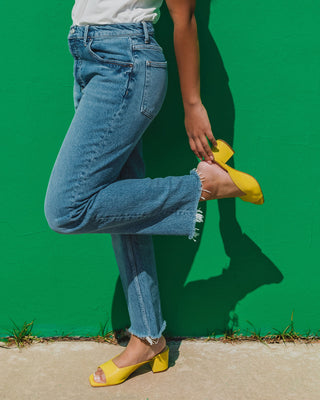 woman wearing yellow slide heels with blue jeans and white top