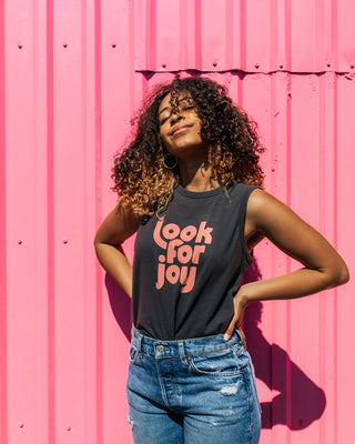 "woman wearing black muscle tank with ""Look for joy"" graphic in pink with blue jeans"