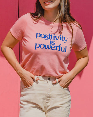 "woman wearing pink tee with ""Postivity is powerful"" graphic with ivory jeans"