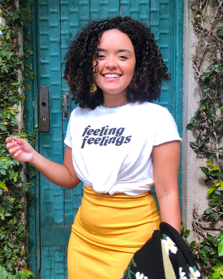 model shown wearing white graphic tee reading feeling feelings