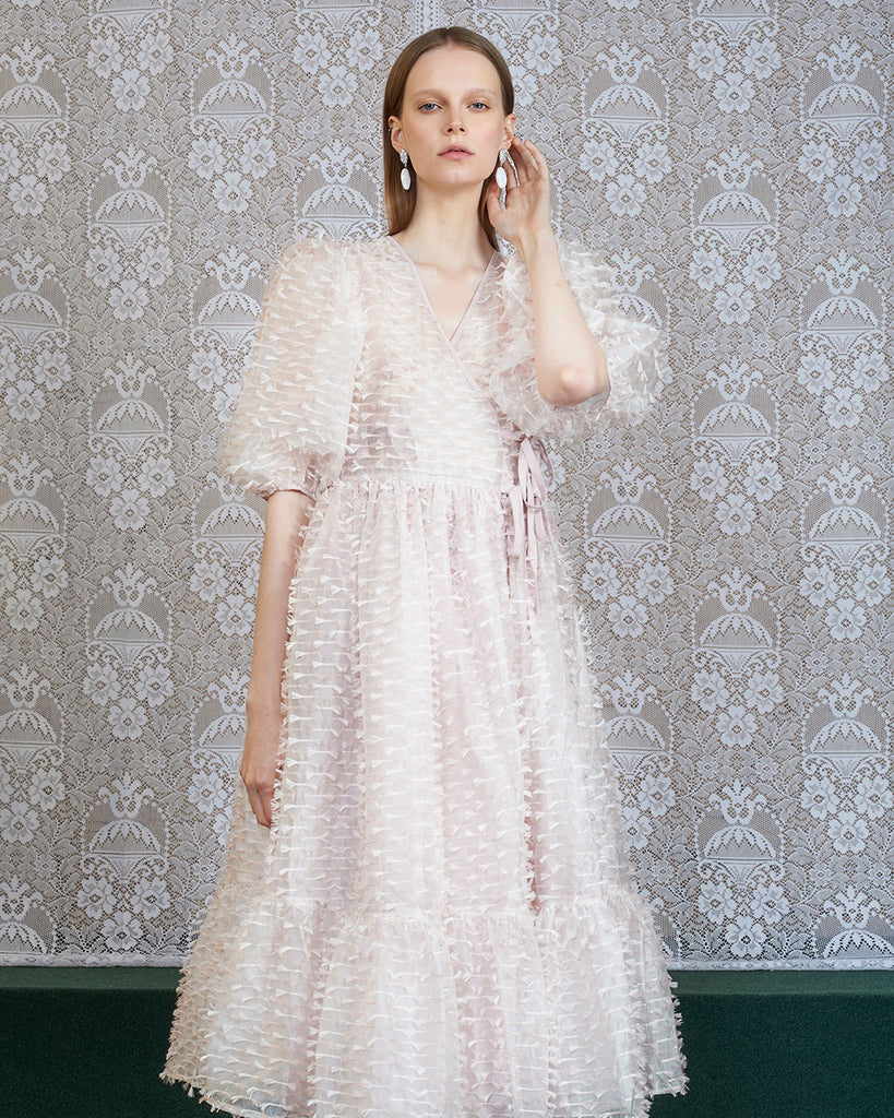 model shown wearing pale pink fuss and feather midi dress