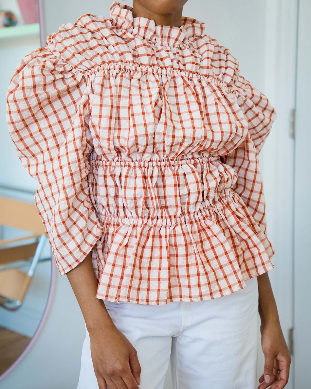 model wearing 3/4 sleeve ruched blouse with mock neck in rust and white check pattern and white pants
