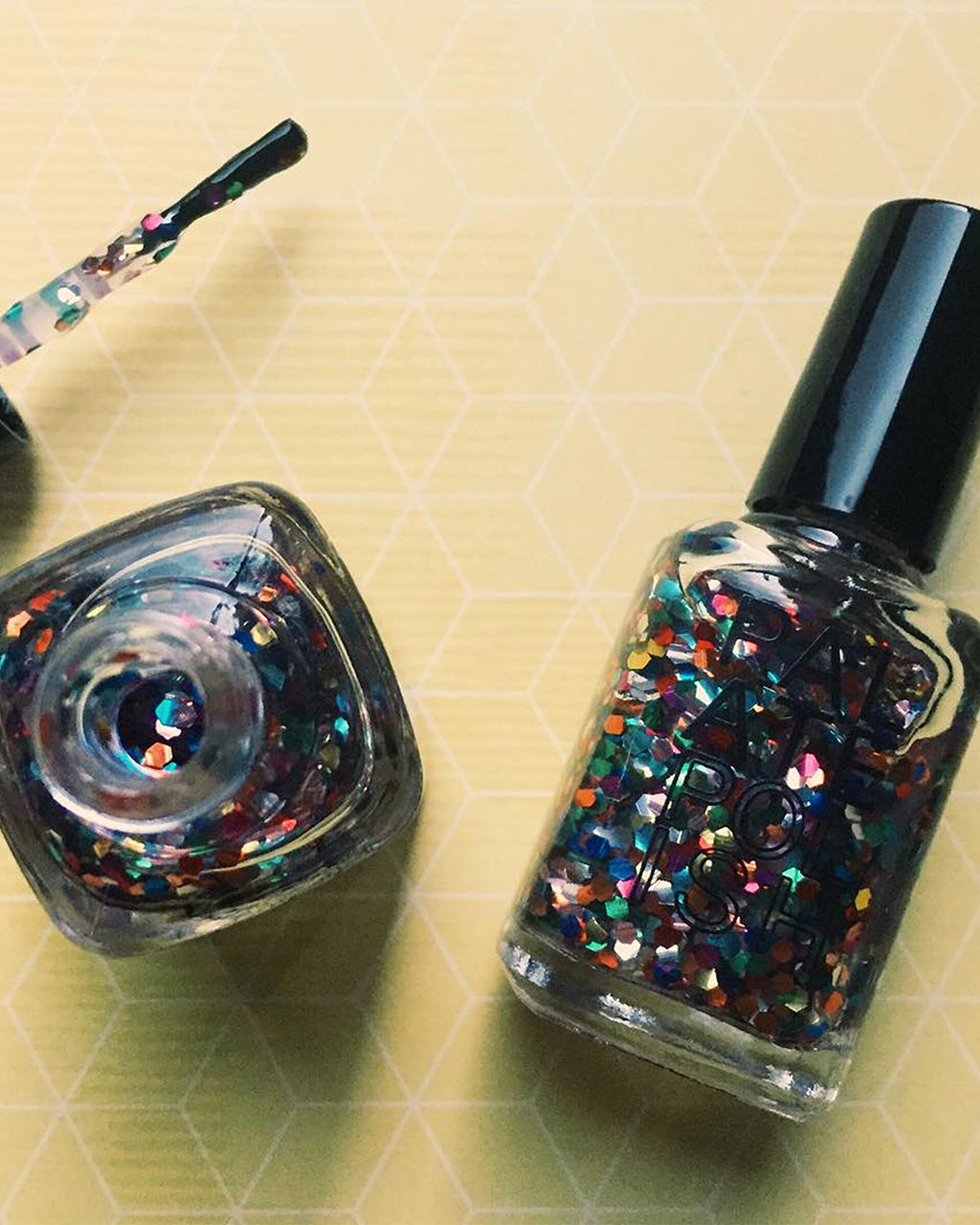 two bottles of gumball nail polish shown on a yellow background